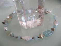 LICHTBLAU   Edle Verbindung aus Aquamarin und Zuchtperlen:   Natürliche, polierte Aquamarinkissen, durch viele kleine 925 Silberteile abgesetzt, und anfacettierte Aquamarinlinsen in Dreiergruppen verschmelzen mit Zuchtperlen in Form von Rauten und Ovalen zu einem wunderschönen Collier, das sowohl zur Jeans als auch zu festlicher Kleidung feine Ergänzung ist.   Sicheren Halt bietet ein länglich-ovaler, hartversilberter Magnetverschluss, halb glänzend und halb matt.