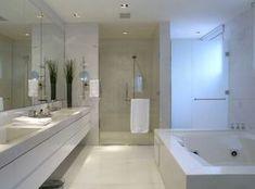 Banheiro todo branco + banheira retangular + bancada com cuba de embutir. Observem que neste caso, por questão de espaço, a banheira não tem escada de acesso, o que torna o uso de pessoas mais idosas arriscado. Projeto Roberto Migotto