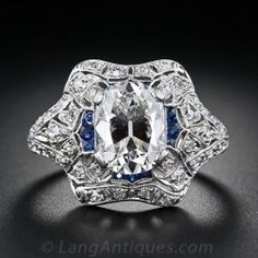 A fantastic 1.75 carat antique cushion-cut diamond is the centerpiece of this all-original Edwardian diamond engagement ring. This exquisitely crafted platinum diamond ring is delicately pierced and set with accent diamonds throughout the ring, with sapphire calibre around the center diamond. Absolutely gorgeous! In a finger size 6 1/2.