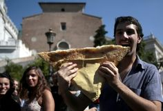 A man bites into a slab of pizza on Michelangelo's steps leading up to the Capitoline Hill, part of a flash mob protesting the new city ordinance that prohibits the consumption of food and drink on artistic and archaeological monuments, 6 October 2012.