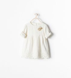 DRESS WITH A BUTTON-TAB EMBROIDERED HEM