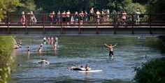 People jump from the bridge linking Blackbird Island to Leavenworth's Waterfront Park Tuesday. World photo/Don Seabrook