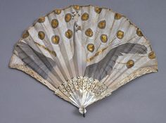 1905-1910 Fan. Painted by Adolphe Thomasse, French. Made for Duvelleroy, Paris. Silk, painted in gouache, with metal sequins; carved, incised, and gilded mother-of-pearl sticks and guards with piqué (inlaid) paste.
