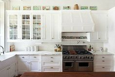 Love this white kitchen - the mix of glass cabinets and the fun art!
