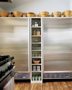 Using Leftover Space: Martha displayed her turn-of-the-century American yellowware mixing bowls above the refrigerator and freezer in her Turkey Hill home; shelving for spices was created in the leftover spaces.