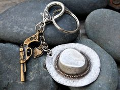 For the cowgirl in love... Here is a fun and funky keychain I made with a large antique silver plated cowboy hat, antiqued bronze heart charm, and antiqued bronze six shooter. Fun stuff. They are hung