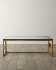 """Horchow coffee table. A hand-wrought iron base with an antiqued gold-leaf finish, inset with tempered glass. 48""""W x 30""""D x 19""""T."""