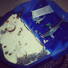 A christmas theme small world play. Fake snow with blue material along with ocean animals and penguins etc.