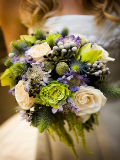 A vintage bridal bouquet of silver brunia thistle, ivory and green roses and green cymbidium orchids with purple scabiosa