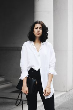 Elisa from the Fashion- and Lifestyleblog www.schwarzersamt.com is wearing a mass customized flare jeans from SELFNATION, a white blouse from WEEKDAY, GOERTZ mules and a celine trio lookalike bag from C&A.  It's a minimal and clean look for the Berlin Fashion Week SS 17 in black and white
