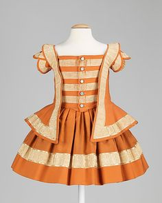 Little boy's orange wool ensemble (dress, without fringed cape) with ivory silk moiré trim, American, 1856. Featured here is a well-documented boy's ensemble, worn by William Henry Eaves for a portrait in 1856, when he was near age three. An elaborate costume like this may well have been made specifically for the portrait and not worn for any other occasion. Another version of this ensemble, which is made of more durable and comfortable material, shows evidence of considerable wear.