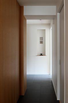 WICの新設に伴いクランクさせた廊下は、LDKへの期待を高める贅沢なアプローチとなりました。玄関に向かって歩くと自ずとニッチが視界に入り、心地のよいアイポイントに。飾った小物に視線が注がれるよう、シンプルかつシャープに仕上げています。夜は間接照明によって、より華やかな雰囲気。床に馬目地に貼ったマットなグレーのタイルが、空間を引き締めつつ、ほどよいリズムを与えています。 専門家:株式会社クラフトが手掛けた、廊下(シンプルと響きあう)の詳細ページ。新築戸建、リフォーム、リノベーションの事例多数、SUVACO(スバコ)