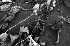 Rwanda, Kibeho A child looks at dead bodies through a razor wire fence in the Kibeho camp. Over 4,000 Hutus were killed on 22/04/1995 during an operation by the Tutsi Rwandan army to clear the Kibeho refugee camp. The tragedy occurred after the army opened fire on the crowd of 100,000 refugees who had been crammed into a small area in the middle of the camp. The crowd panicked and tried to run, crushing thousands in the melee. Many more were shot and macheted by the Rwandan Patriotic Army…