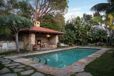 Mediterranean Swimming Pool with exterior stone floors, Raised beds, outdoor pizza oven, Fence