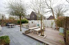 Onderhoudsvriendelijke tuin. Mooie grote zwarte tegels, en leuk detail zijn de spots in de houten vloer.: