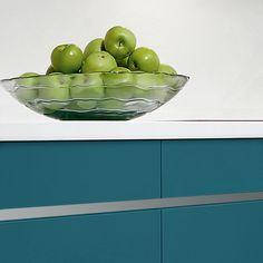 Modelo lacado en acabado azul petróleo con Gola corrida, eliminando el tirador de los elementos bajos.