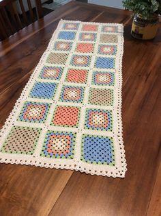 Caminho de mesa de crochê colorido.