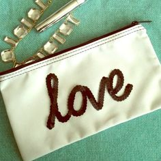 """Love"" Sequin Clutch This handcrafted ""love"" clutch features glued glittery black sequins that is bonded with a permanent fabric adhesive that is washable.  Use the bag as a clutch or cosmetic bag for your everyday essentials! The bag is 10.5 by 5.5 inches. Bags Clutches & Wristlets"
