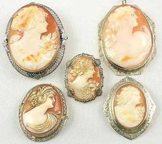 A grouping of white gold and sterling silver mounted carnelian shell Edwardian antique cameos. Four antique cameos are brooches, with one antique cameo pendant upper right corner.