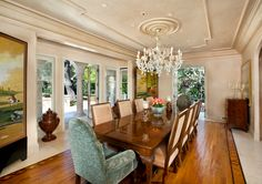 Banquet-sized formal dining room with inlaid wood flooring outlined in parquetry and travertine; Venetian glass chandelier from a ceiling medallion; French doors to rear and side terraces.  #chandeliers