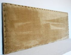 Tan velvet upholstered headboard, large nail trim along the border. About 1,5 inches thick, soft enough to lean against and read a book. Queen