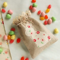 little favor or keepsake bag decorated with a bunny applique and edged with lace