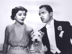 America's favorite couple, Nick and Nora Charles, portrayed by the lovable Myrna Loy and William Powell, with their canine costar, Asta, in The Thin Man (1934).