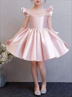 Girls Pink Beaded Flutter Sleeve Special Occasion Dress with Large Bow She will be the talk of this year's extravaganza. This radiant shimmery pink dress has a beaded c Baby Girl Party Dresses, Dresses Kids Girl, Kids Outfits, Flower Girl Dresses, Kids Frocks Design, Kids Dress Patterns, Frock Design, Pink Dress, Kids Fashion