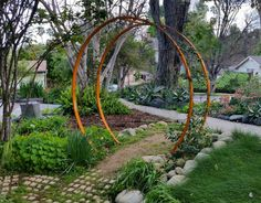 A natural garden pathway is always more welcoming with a Gracie Modern Arbor by TerraTrellis.com