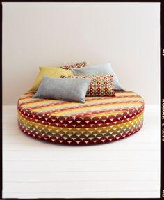 Jane Churchill Caro Rainbow velvet fabric on an ottoman.