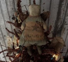 SWEET CUTE PRIMITIVE ANGEL TREE TOPPER or tuck in a bowl with some greens. Rag stuffed. Hand painted gray dress. Brown fabric wings with hand penciled face. Old feed sack with stamped BELIEVE. Measures 7 3/4 T ♥