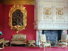 This Louis XIV or Regency Rococo Style drawing room features beautiful fabric walls, a circular carved marble mantel with white panel board with gold fleur de lis motifs, floral designs and family crest. The columns of either side are Italian influence but complimented by the Regency Style Furniture.,