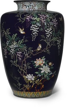 A cloisonné enamel vase, worked in silver wire and colored enamels on a dark blue ground with birds in flowering wisteria above blossoming peonies, Meiji period (late 19th century). Height: 18cm