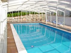 A white pool enclosure with glass panels in the Venezia model line brings a cheerful, bright ambiance to this solarium/swimming pool, courtesy of Pool & Spa Enclosures.