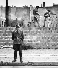 A West Berlin police officer stands in front of the concrete wall dividing East and West Berlin at Bernauer Strasse as East Berlin workers add blocks to increase the height of the East German barrier Oct. 7, 1961.