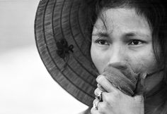 A young South Vietnamese woman covers her mouth as she stares into a mass grave where victims of a reported Viet Cong massacre were being exhumed near Dien Bai village, east of Hue, in April 1969. The woman's husband, father and brother had been missing since the Tet Offensive, and were feared to be among those killed by Communist forces. (Photo by AP Photo/Horst Faas).