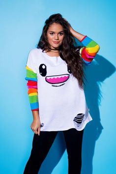 Actress Madison Pettis in our SO SO Happy Lucky sweater with rainbow sleeves and cute smiling monster face.
