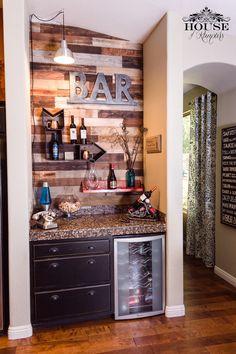 Bar moderno, com parede revestida de madeira, decorado com letra do nome do proprietário, prateleiras e móvel restaurado.