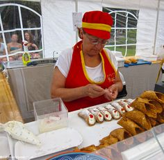 A Sicilian woman pipes ricotta into cannoli. Click to see 5 Italian Street Foods to Try!