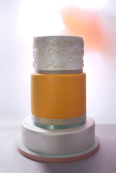 JOSEFA | Charm City Cakes - Three tier stacked cake. Bottom tier is pearl white color. Second tier is goldenrod color with pearl and teal ribbon accent. Top tier is pearl white with stunning pearl designs. From our Summer 2013 Collection.
