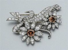 Fancy Colored Diamond and Diamond Flower Clip-Brooch   Platinum, designed as a spray bouquet accented with 2 round Fancy to Fancy Dark Orangy Brown diamonds*, approximately 1.90 cts., set throughout with 104 round and 37 baguette diamonds, approximately 5.50 cts., circa 1945, approximately 12.8 dwt.
