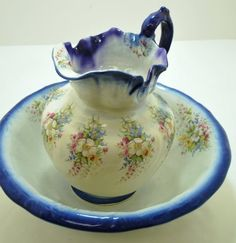 VINTAGE WASH BOWL AND PITCHER IN WHITE AND BLUE, DECORATED WITH FLOWERS.