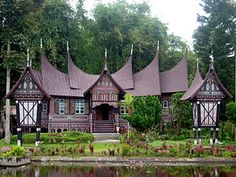 Rumah gadang in the Pandai Sikek village of West Sumatra, with two rice barns