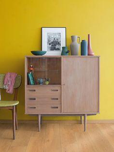 Rincón con aparador en madera sobre pared pintada en amarillo mostaza