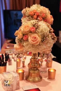 Blush, peach and white rose centerpieces with gold table accents. Gold votive candles. Almost a vintage inspired look.