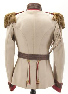 Back side view of an Imperial Russian Horse Guard Regiment officer's tunic or 'Koller', circa 1900. White boiled wool tunic with red cuffs and piping. Silver bullion braid mixed with orange and bordered in blue trim on collar, front and cuffs. Collar and cuffs also display silver bullion Litzen, those on the cuffs with gold double-headed eagle buttons. Complete with gold bullion fringed epaulettes faced in red with applied gold tone crown and cipher of Nicholas II.