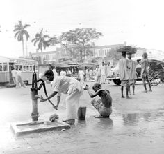 Two men taking their morning wash at a public pump on the streets of Calcutta, India.
