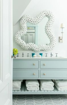 A white seashells mirror will definitely catch your eye in this white and blue beach style bathroom boasting a light blue washstand placed on white and gray mosaic floor tiles, fitted with a slated towel shelf, and finished with rope knobs and white quartz countertop.