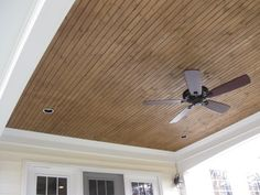 The interior of this open porch includes a tongue and groove pine ceiling  stained in a warming hue, along
