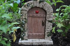 Welcome magical fairies, pixies and gnomes into your home or garden with this enchanting fairy door, featuring the look of old wood, cobblestones and featuring a red heart. Fairy Garden Houses, Miniature Fairy Gardens, The Hobbit, Craft Supplies, Whimsical, Miniatures, Doors, Bird, Outdoor Decor